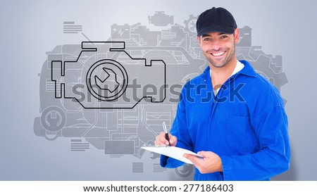 Handyman in blue overall writing on clipboard against grey vignette - stock photo