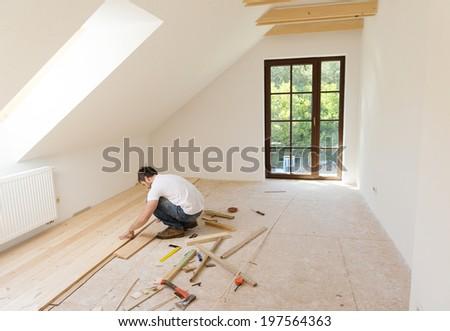 Handyman installing wooden floor in new house - stock photo
