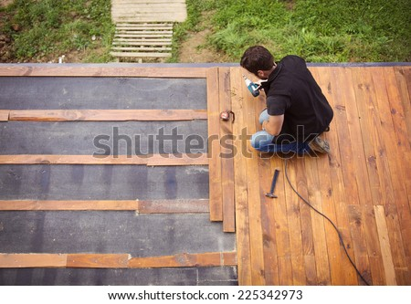 Handyman installing wooden flooring in patio, working with drilling machine - stock photo