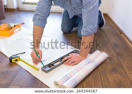Handyman measuring wallpaper to cut - stock photo