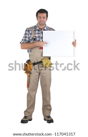 Handyman pointing to poster - stock photo
