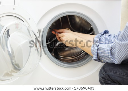 handyman repairing a washing machine - stock photo