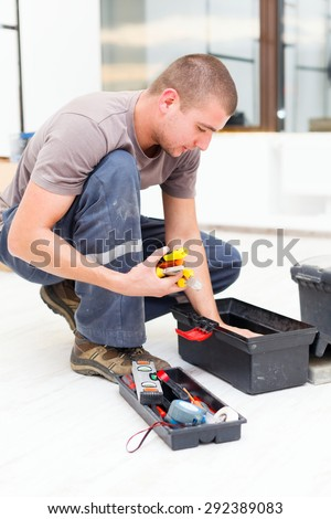 Handyman searching in his tool box for the necessary tools. - stock photo