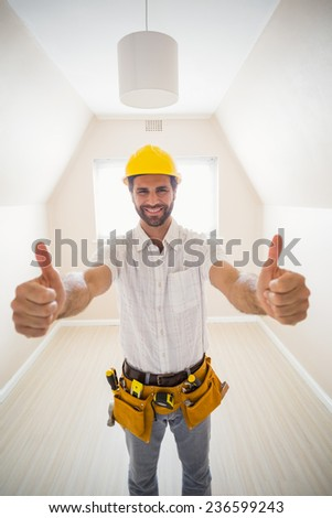 Handyman smiling at camera in tool belt in a new house - stock photo