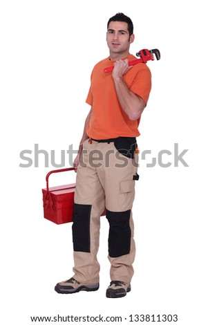 Handyman stood with wrench and tool kit - stock photo