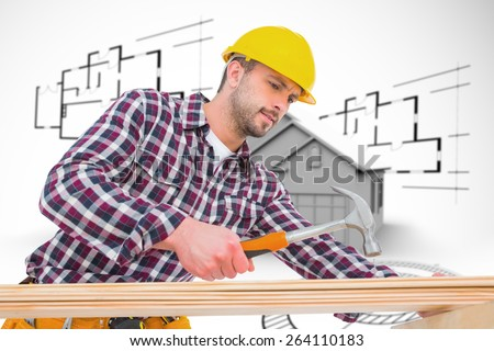 Handyman using hammer on wood against house in grey with architect plans - stock photo