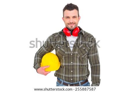 Handyman with earmuffs holding helmet on white background - stock photo