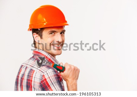 Handyman with wrench. Rear view of handsome young handyman with carrying wrench on shoulder and looking over shoulder while standing against grey background - stock photo