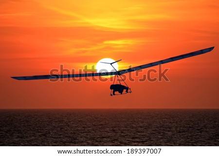hang glider at sunset - stock photo