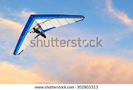 Hang glider fling over the ocean at sunset - stock photo