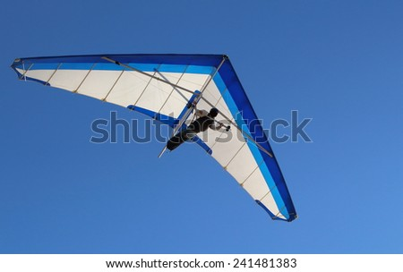 Hang Glider flying in the sky on a sunny bright blue day - stock photo