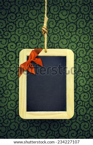 Hanged old slate board with Christmas bow in the corner - stock photo