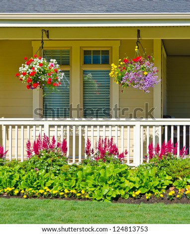 Hanging baskets of flowers at the front porch. Landscape design. - stock photo