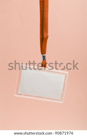 Hanging blank business plastic badge with orange neck strap against rosy background - stock photo