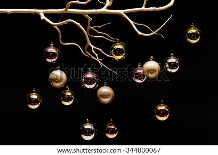 Hanging colorful Christmas balls on black background - stock photo