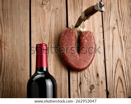 Hanging dry spicy sausage with a red wine bottle, close up - stock photo