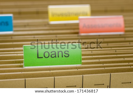 Hanging file folder labeled with Loans - stock photo