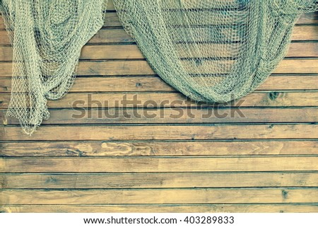 Hanging Fishnet On The Rustic Wood Slats Wall Background. Grunge Wooden Background With Old Fish Net - stock photo