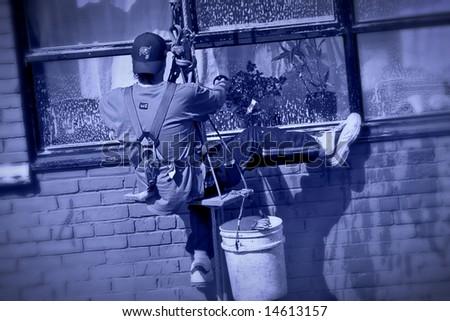hanging from ropes washing windows - stock photo