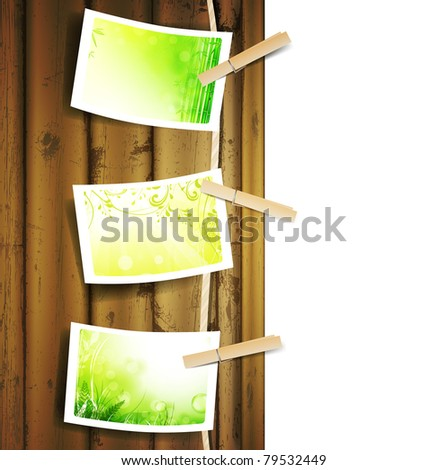 Hanging green foliage photos pinned to a Rope near wooden background over white - stock photo