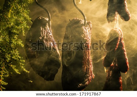 Hanging ham in the smokehouse - stock photo