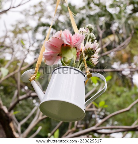 Hanging of flowers and watering can decorate in garden - stock photo