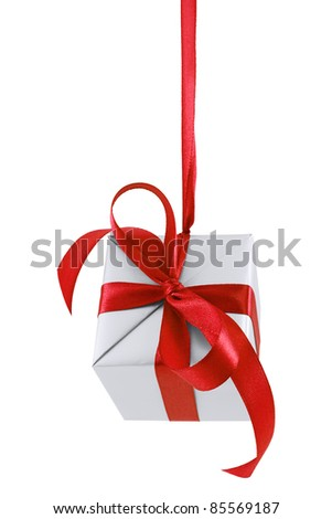 Hanging on a ribbon silver gift wrapped present with red satin bow isolated on white - stock photo