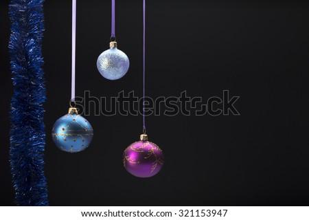 Hanging three colorful Christmas balls on black background - stock photo