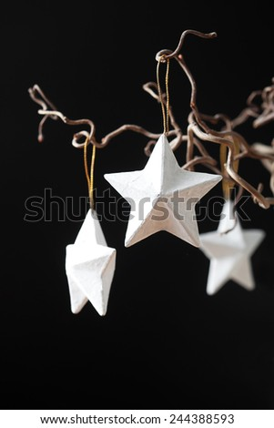 Hanging white Christmas stars on black background - stock photo