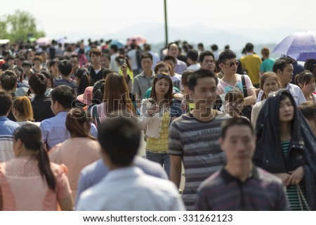 HANGZHOU, CHINA, MAY 1: Crowd walking along the lake in Hangzhou on the 1st of May, the Labour Day in China, 2013 (Selective focus) - stock photo