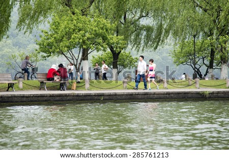 HANGZHOU, CHINA - MAY 3, 2015: Tourists enjoying by the Xihu (West Lake). West Lake has influenced poets and painters throughout China's history for its natural beauty and historic relics. - stock photo