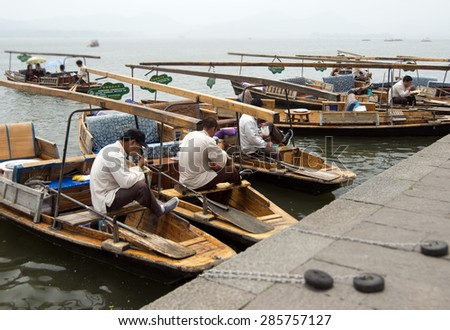 HANGZHOU, CHINA - MAY 3, 2015: Traditional Chinese wooden boats with boatmen on the Xihu (West Lake) taking a break and having some lunch. The lake has influenced poets and painters throughout China. - stock photo