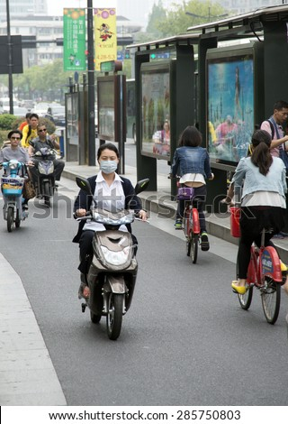 HANGZHOU, CHINA - MAY 3, 2015: Woman riding an electric motorcycle with protection against the pollution.  - stock photo