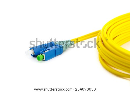 Hank of yellow optic cable with blue patch cord connectors isolated on white background - stock photo