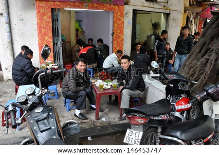 HANOI - FEB 19: Unidentified Vietnamese men drinking local beer called Bia Hoi in Hanoi. The beer is brewed daily and each bar gets a fresh batch every day. On Feb. 19, 2013 in Hanoi, Vietnam - stock photo