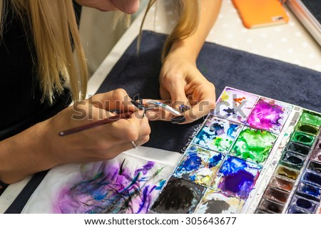 Hanoi Vietnam August 8 2015 the artist designed and painted onto nails.Beautiful manicure process. Nail polish being applied to hand - stock photo