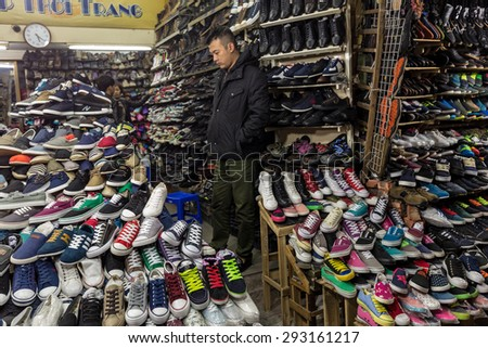 HANOI, VIETNAM, DECEMBER 15, 2014 : An undecided man is taking a look in a shop specialized in the selling of shoes in Hanoi, Vietnam - stock photo