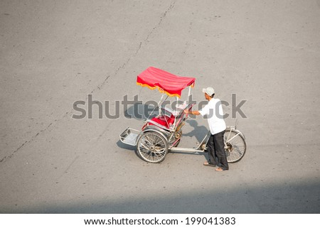 Hanoi, Vietnam, june 6, 2014: Life in vietnam- Cyclo beside Hoankiem lake( sword lake) in hanoi, vietnam. Cyclo is the tourist's farvourite vehicle transportation in vietnam - stock photo