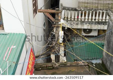 Hanoi, Vietnam - Mar 15, 2015: Electric wires cross houses in Hanoi, Vietnam. Large collections of electric wires are a common site in Hanoi. - stock photo