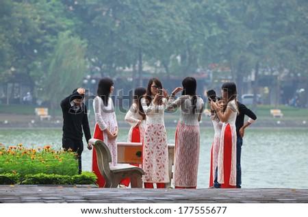 HANOI, VIETNAM - NOV 27, 2013: A group of unidentified newly graduated students posing on the bank of Hoan Kiem lake.  - stock photo