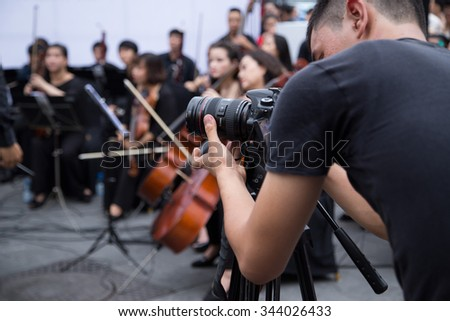 Hanoi, Vietnam - Nov 22, 2015: An Asian cameraman filming an outdoor live classic concert music by Asian composers performing on the side walk of an old quarter street in Hanoi capital city. - stock photo