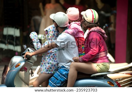 HANOI,VIETNAM - OCTOBER 12 : Vietnamese riding motorcycle overload and heavy   common on the street in Old town on October 12,2014 in Hanoi city,Vietnam. - stock photo