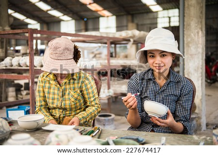 HANOI, VIETNAM - SEP 24, 2014: Unidentified Vietnamese women work at the ceramic workshop. Ceramic art is very popular in Asian culture - stock photo