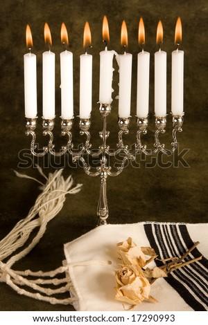 Hanukkah candle-holder and a jewish prayer shawl - stock photo