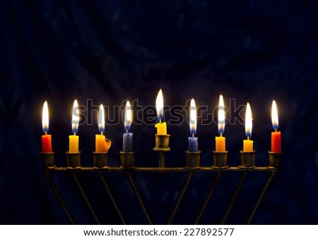 Hanukkah menorah (nine-branched candelabrum) with burning colored candles on a dark blue background - stock photo