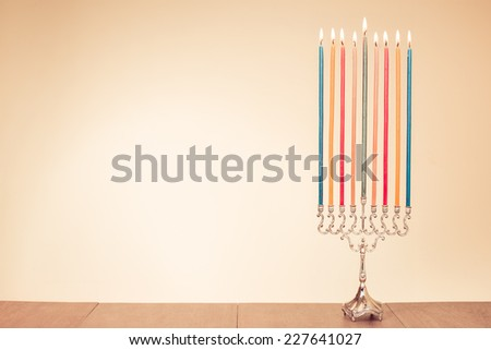 Hanukkah menorah with burning color candles for holiday greeting card background - stock photo