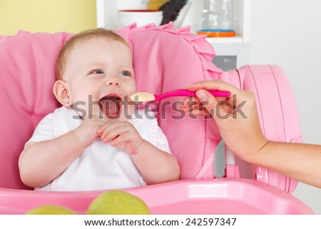 Haply baby girl is feeded by mother - stock photo