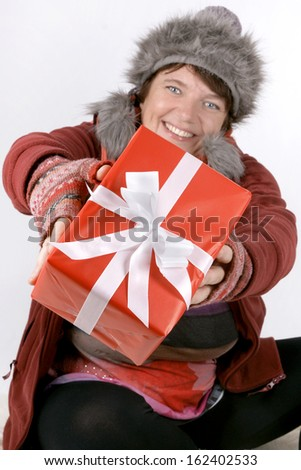 Happily smiling woman offering a christmas present  - stock photo
