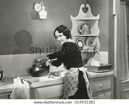 Happily washing pots and pans - stock photo