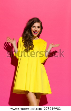Happiness Against Pink Wall. Laughing beautiful girl in yellow mini dress posing with arms outstretched. Three quarter length studio shot on pink background. - stock photo